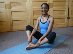 African American teacher training student in a yoga pose.
