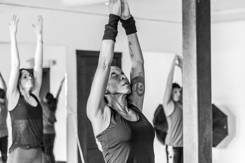 Woman lifts arms in a grad gesture, one of the five reasons to practice yoga.