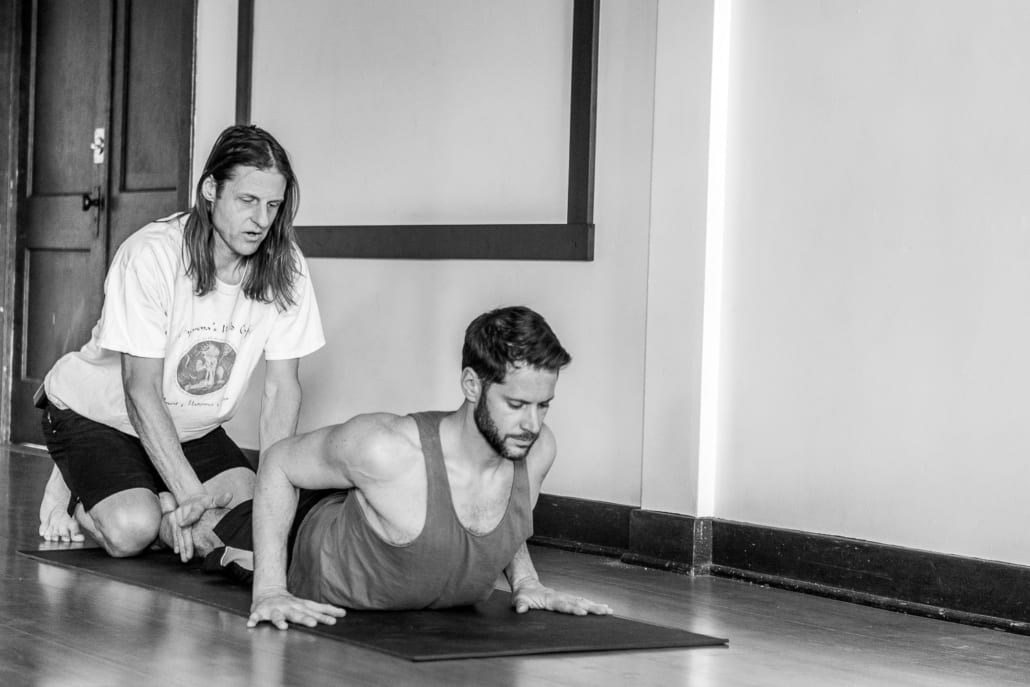 A man demonstrates cobra pose while teaching yoga.