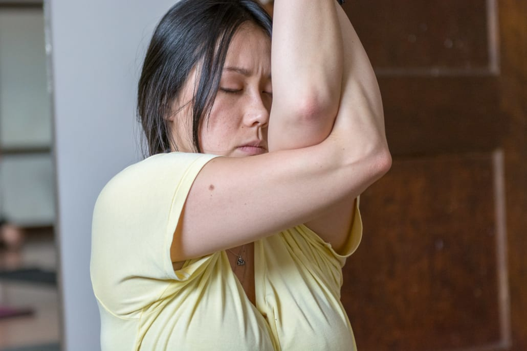 A teacher training student binds her arms in a yoga pose.