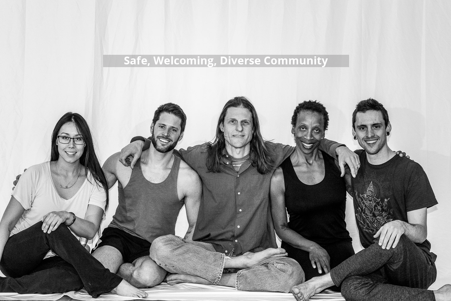 Diversity of Denver Yoga Underground students sitting in a row and smiling.