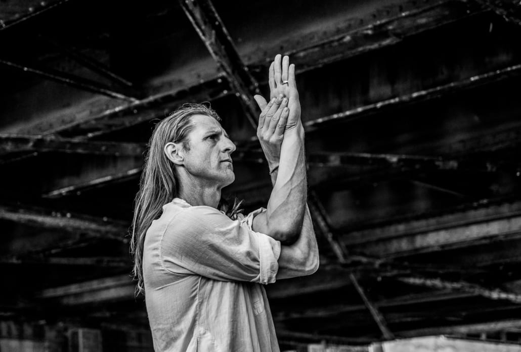 Lead yoga teacher training Derik Eselius standing under a bridge with his arms crossed in a yoga pose.