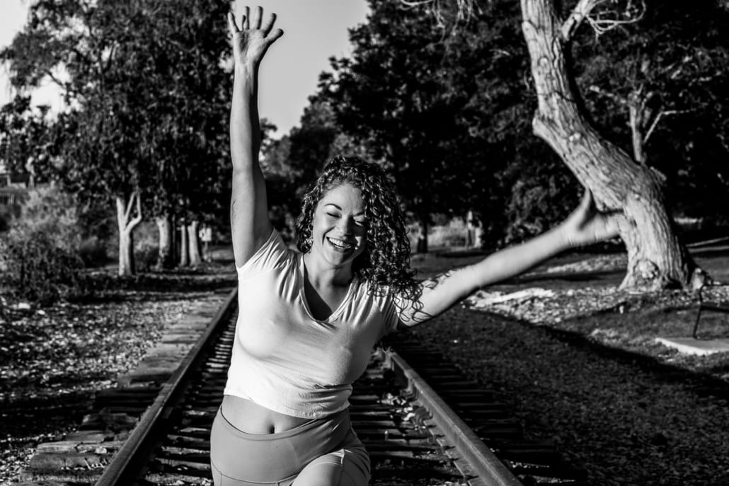 A woman smiles while doing a yoga pose on the railroad tracks.
