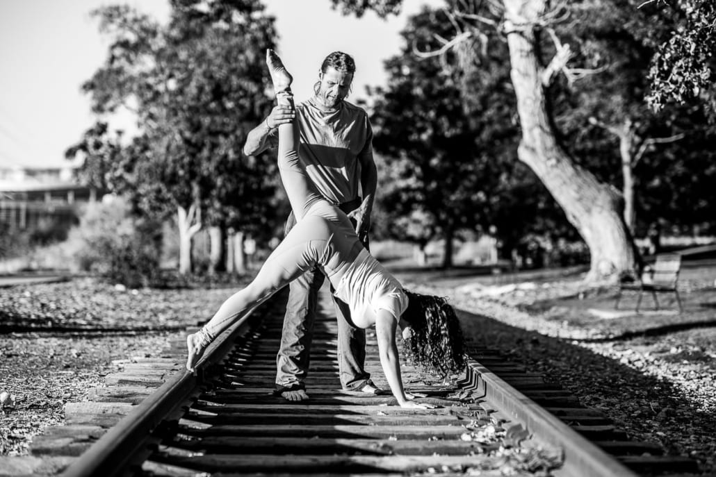 A man teaching yoga to a woman on the railroad tracks.
