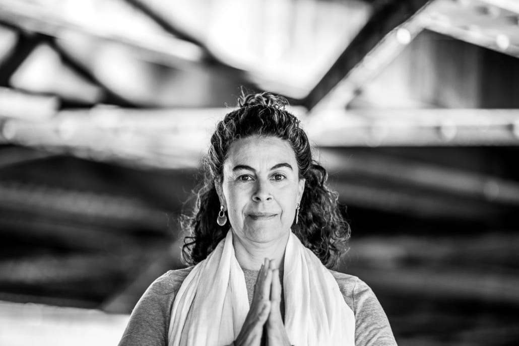 Beth Sanchez, lead ayurveda teacher for the Denver Yoga Underground, stands under a bridge with palms joined.