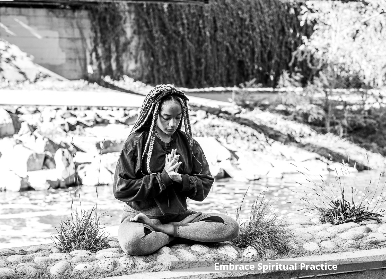 African American woman meditating by the side of a river in Denver Colorado
