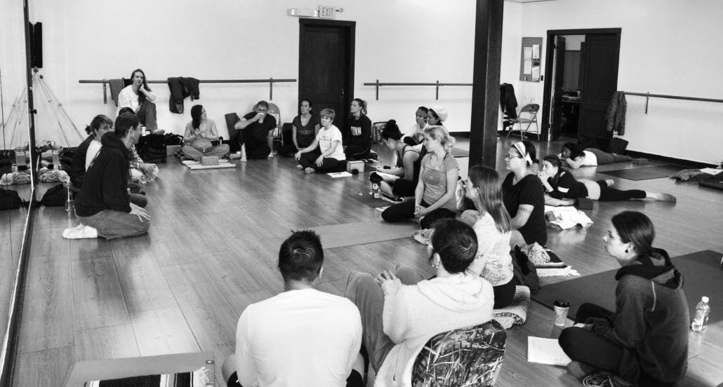 Yoga students sit in a circle to discuss about us all.