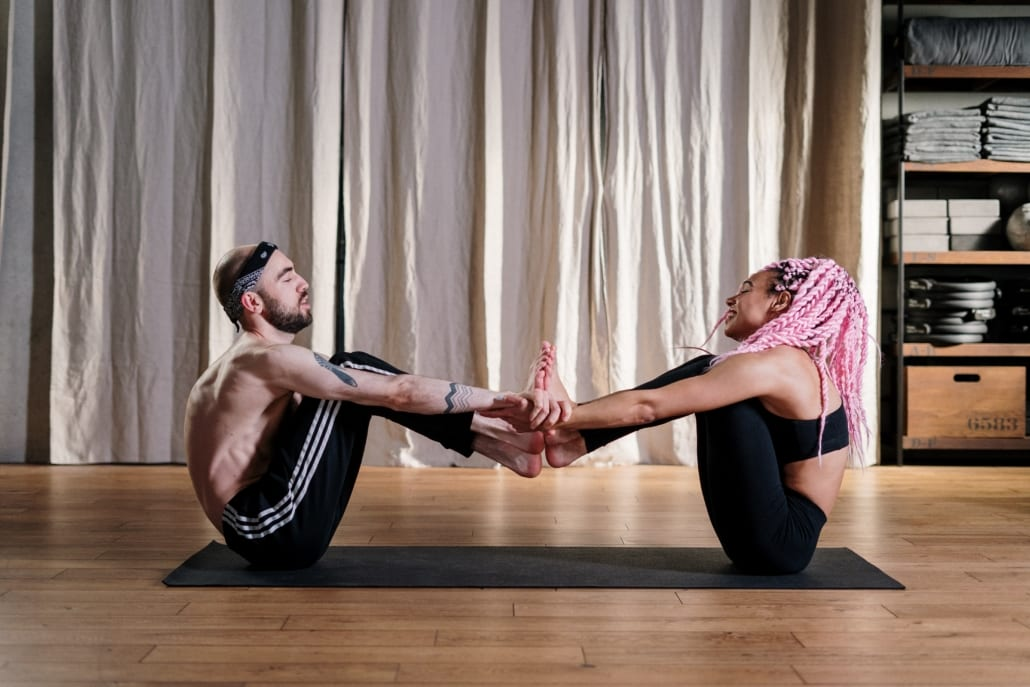 woman with pink hair teaches yoga to a male student
