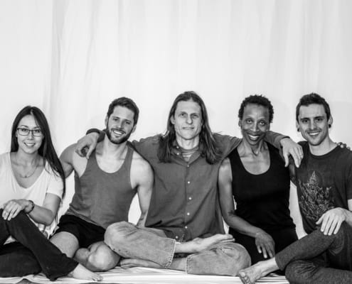 group of yoga students gather in an embrace