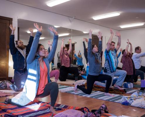 yoga workshop students raise arms overhead